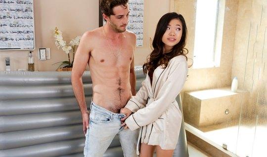 Обнаженная азиатка обмазывает свое тело маслом и делает небритому парню минет