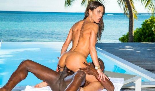 На берегу моря красивая брюнетка скачет киской на члене темнокожего парня